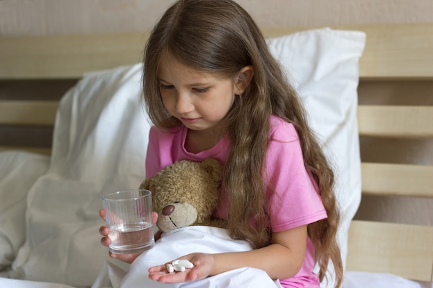 Menina fofa e triste sentada na cama segurando um copo de água, pílulas, remédios e ursinho de pelúcia