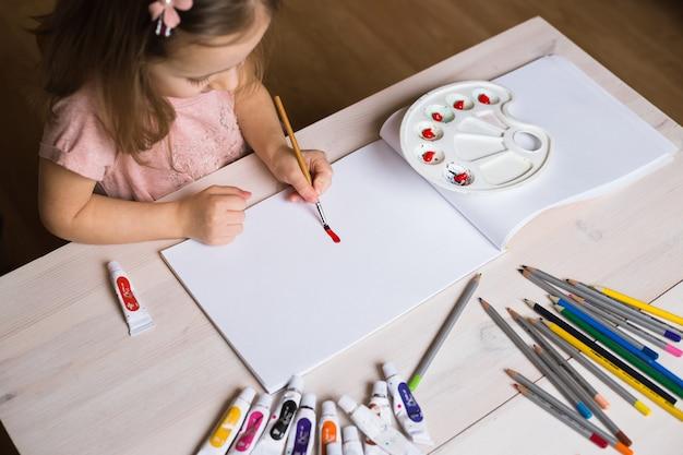 Menina fofa pintando foto no interior da casa