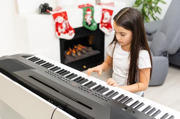 Menina fofa tocando melodia de natal no piano, comemoração de feliz natal, boas festas sazonais