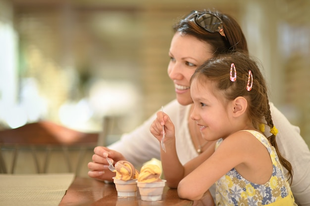 Menina fofa tomando sorvete com a mãe