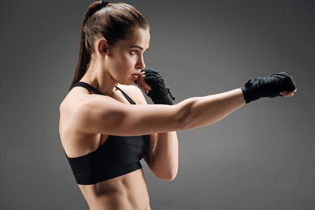 Menina forte boxe em um cinza
