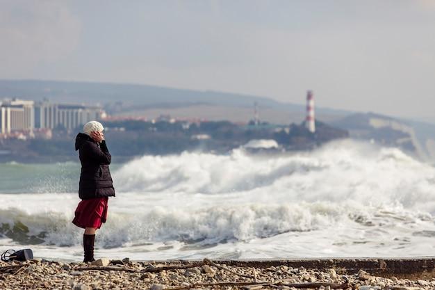 Menina fotografa grandes ondas de tempestade perto de um farol e rochas. a menina está vestida com uma jaqueta preta, chapéu de malha branco, saia longa cor de vinho e botas pretas.