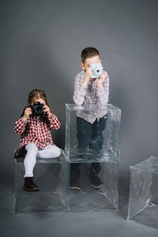 Menina fotografando com câmera e menino fotografando com câmera instantânea vintage