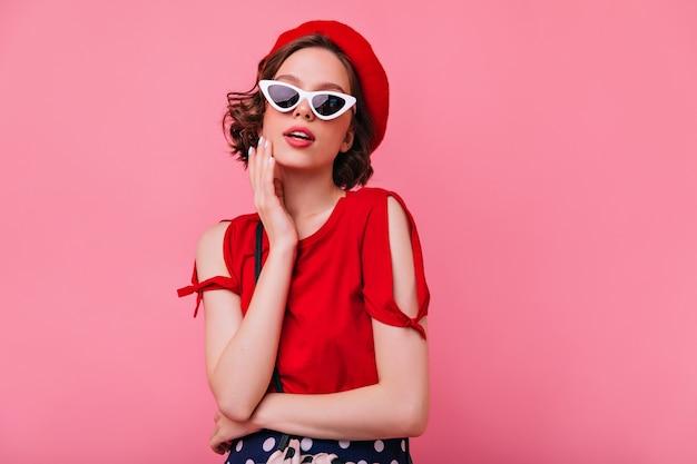 Menina francesa inspirada com cabelo escuro encaracolado em pé. maravilhosa mulher caucasiana na boina vermelha, olhando com interesse.