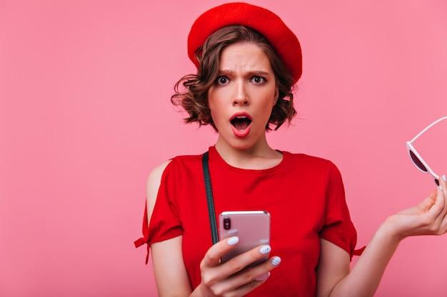 Menina francesa surpresa com manicure branca segurando smartphone. jovem espantada com um penteado elegante, posando com o telefone.
