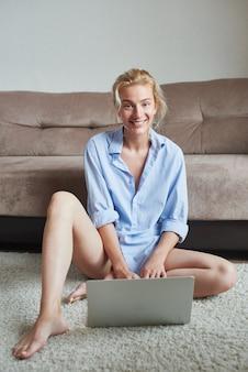 Menina freelancer com laptop trabalha em casa no chão, educação a distância