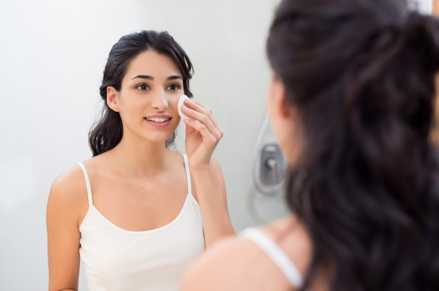 Menina fresca e saudável removendo a maquiagem do rosto com uma almofada de algodão