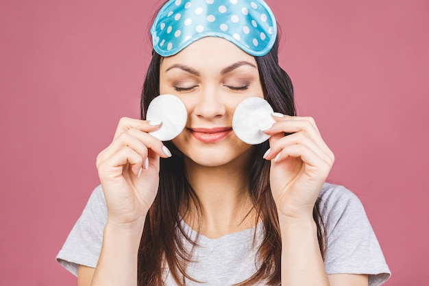 Menina fresca saudável remover maquiagem do rosto com almofada de algodão. mulher de beleza limpando o rosto com almofada de cotonete isolada em fundo rosa. cuidados com a pele e o conceito de beleza. máscara de dormir.