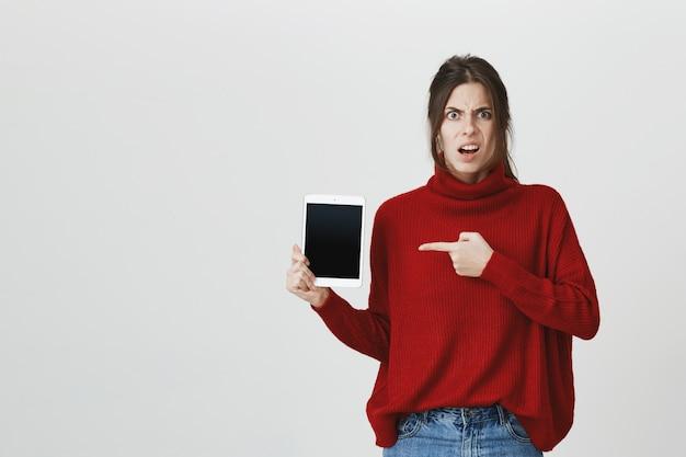 Menina frustrada, encolher e apontar a tela do tablet digital