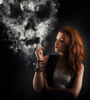 Menina fumando um cigarro formando uma caveira