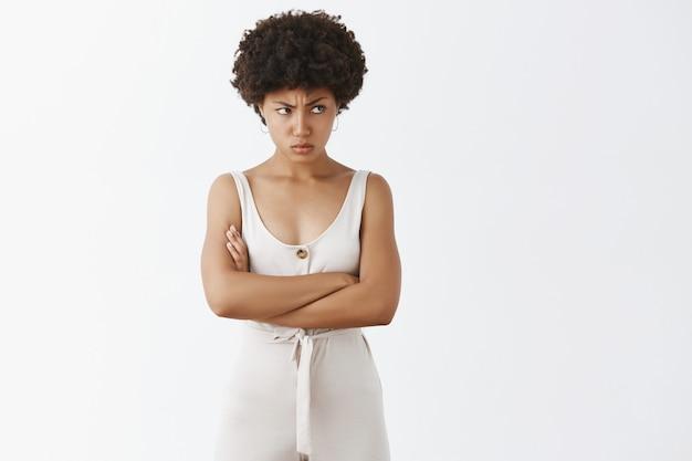 Menina furiosa e elegante posando contra a parede branca