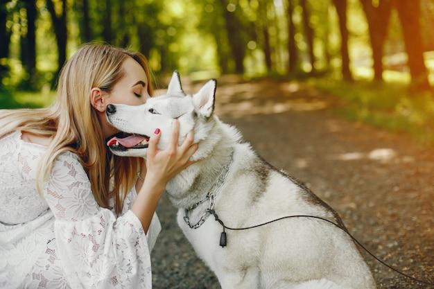 Menina gentil com cabelo claro vestido de branco está jogando junto com seu cachorro