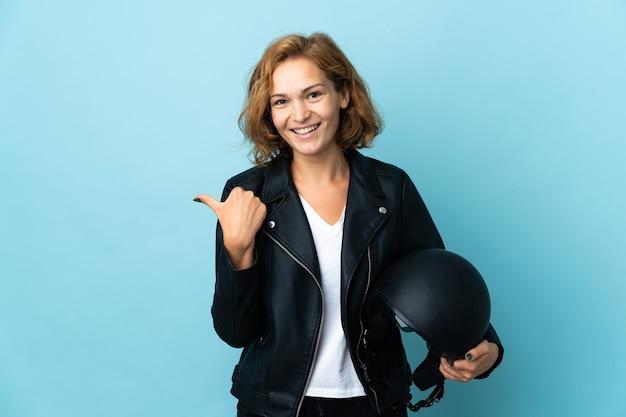 Menina georgiana segurando um capacete de motociclista isolado em uma parede azul apontando para o lado para apresentar um produto