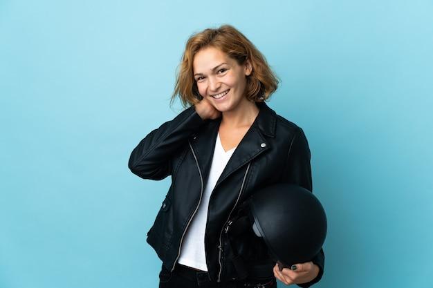 Menina georgiana segurando um capacete de motociclista isolado em uma parede azul rindo