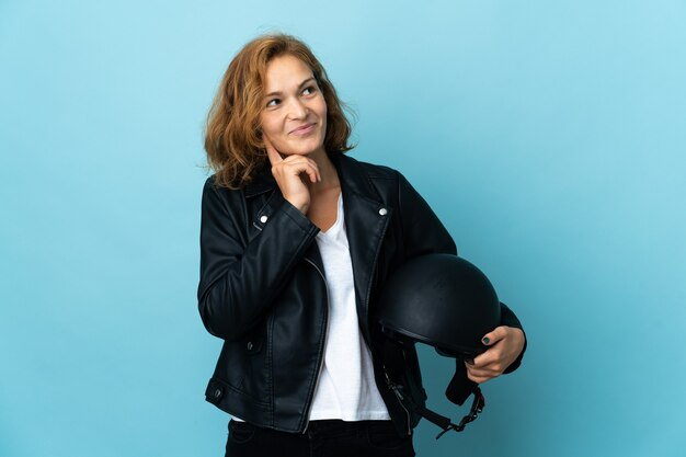 Menina georgiana segurando um capacete de motociclista isolado em uma parede azul, tendo uma ideia enquanto olha para cima