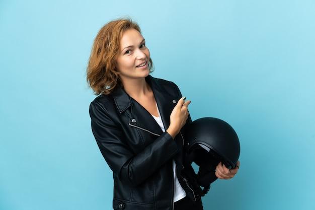 Menina georgiana segurando um capacete de motociclista isolado na parede azul apontando para trás