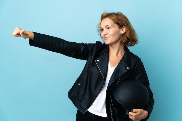 Menina georgiana segurando um capacete de motociclista isolado na parede azul e fazendo um gesto de polegar para cima