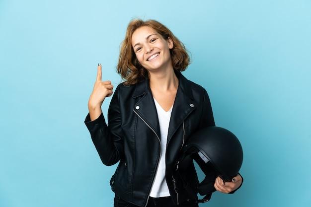 Menina georgiana segurando um capacete de motociclista isolado na parede azul, mostrando e levantando um dedo em sinal dos melhores
