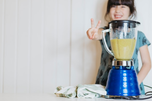 Menina gesticulando ao fazer smoothie