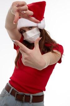 Menina gesticulando com as mãos máscara médica estúdio feriado natal