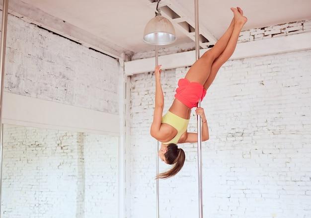 Menina gira em torno do pólo durante a execução de dança ou yoga no estúdio com paredes de tijolos brancos