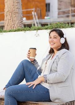 Menina gordinha tomando um café ao ar livre