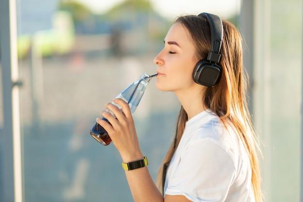 Menina gosta de beber refrigerante em ouvir música