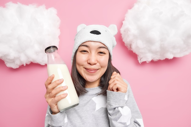 Menina gosta de leite não pode esperar para beber vai tomar café da manhã depois de acordar usa chapéu e pijama posa dentro de casa em rosa