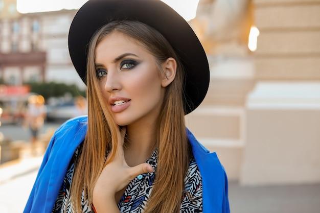 Menina graciosa com roupa elegante de outono, caminhando durante as férias na europa. bolsa de couro elegante. jaqueta azul e chapéu preto.