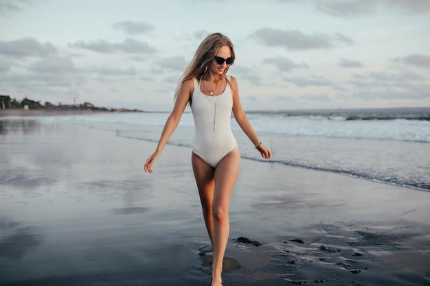 Menina graciosa olhando para o mar com um sorriso enquanto caminhava ao lado. retrato ao ar livre de mulher jovem e bonita em trajes de banho se divertindo na praia selvagem.