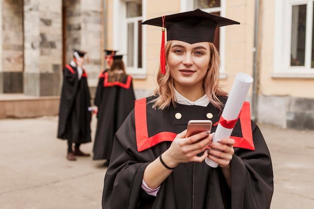 Menina graduada que verifica móvel