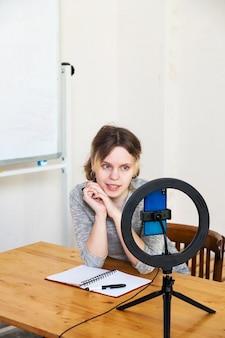Menina gravando vídeo no smartphone e se acendendo com uma lâmpada circular
