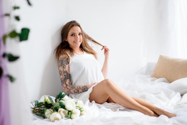 Menina grávida bonita em um vestido branco e com um ramalhete das flores.