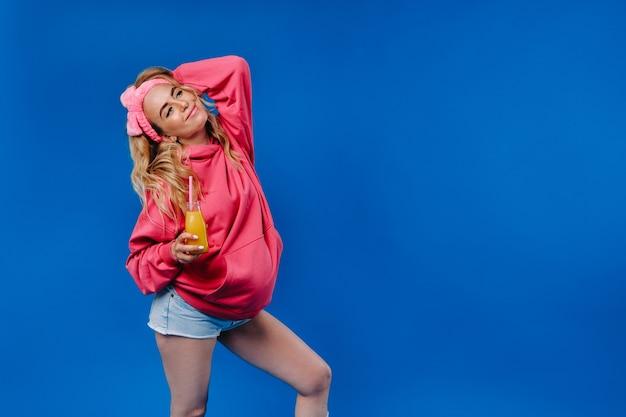 Menina grávida com roupas cor de rosa com uma garrafa de suco em um fundo azul.