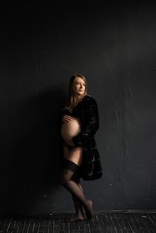 Menina grávida contra uma parede preta