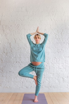 Menina grávida em um terno azul esportes fica em pose de ioga, retrato de corpo inteiro