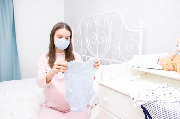 Menina grávida em uma máscara médica protetora olha as coisas para um recém-nascido. expectativa de um filho, maternidade.