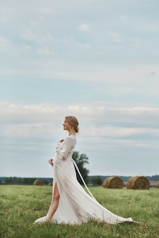 Menina grávida entra em um campo perto de palheiros em um vestido longo branco, uma mulher sorri e mantém as mãos sobre o estômago