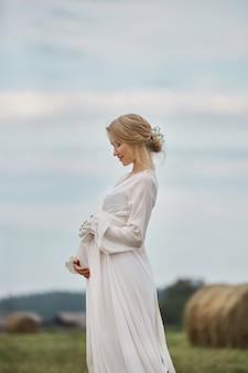 Menina grávida entra em um campo perto de palheiros em um vestido longo branco