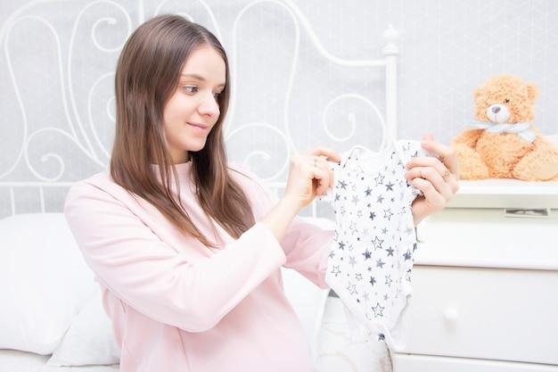 Menina grávida olha as coisas para um recém-nascido. expectativa de bebê, maternidade.