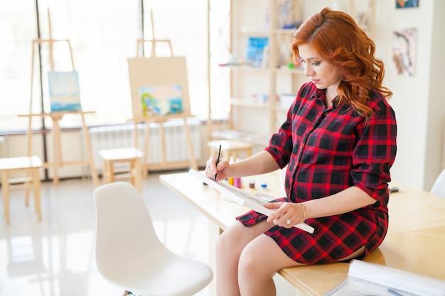 Menina grávida pinta uma foto de sua futura família.