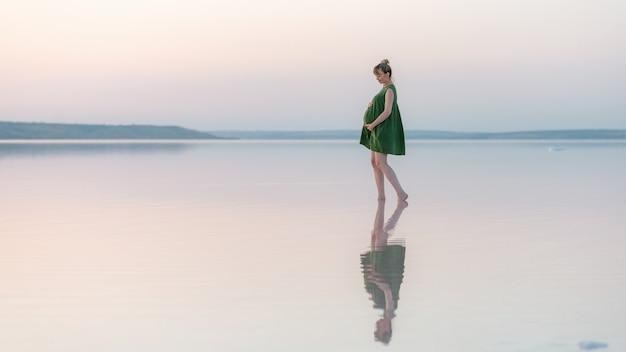 Menina grávida posando ao pôr do sol na água com um reflexo. pôr do sol incrível sobre um lago raso.