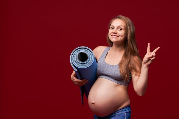 Menina grávida segurando um tapete de esportes nas mãos dela