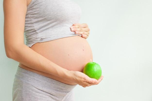 Menina grávida segurando uma maçã verde