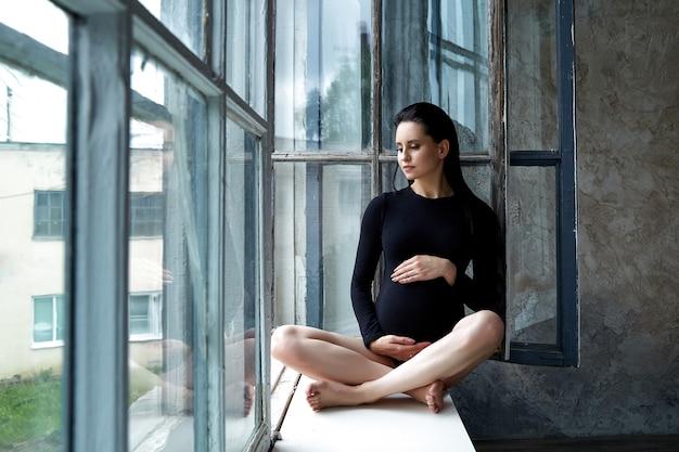 Menina grávida senta-se com os olhos fechados, perto da janela