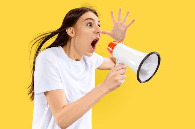 Menina gritando com o porta-voz. belo retrato feminino de meio comprimento isolado na parede amarela. jovem mulher sorridente. espaço negativo. expressão facial, conceito de emoções humanas.