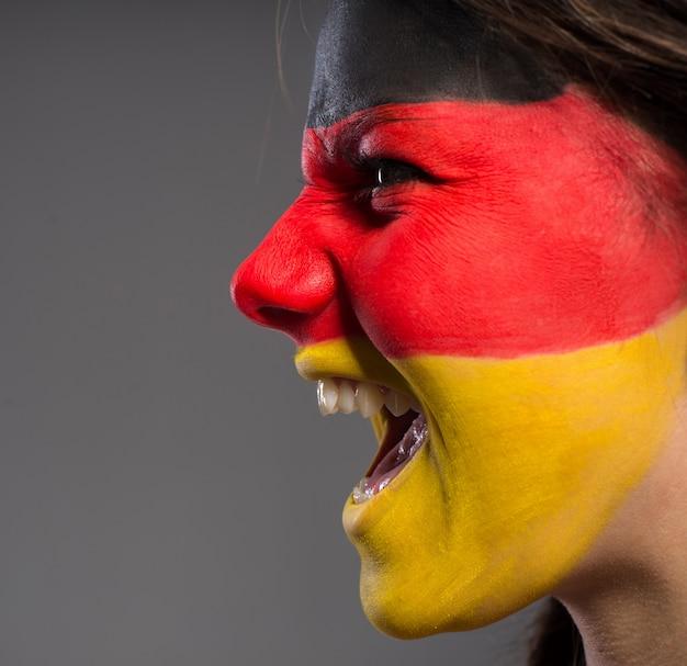 Menina gritando com uma bandeira pintada no rosto.
