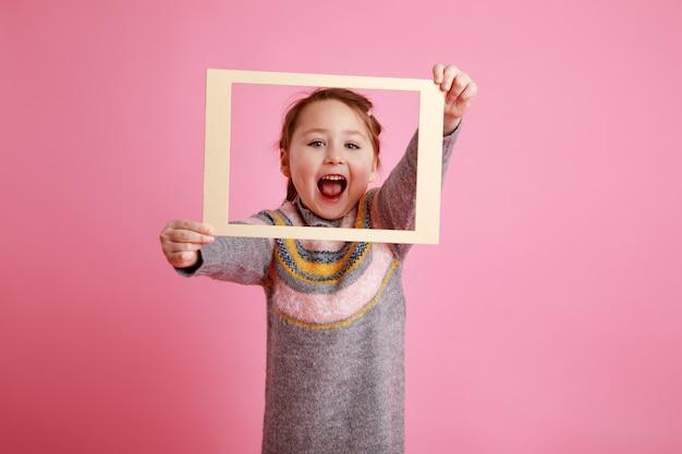 Menina gritando em um vestido quente olhando através da moldura na rosa bachground