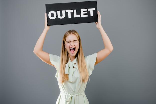 Menina gritando feliz com sinal de saída isolado sobre cinza