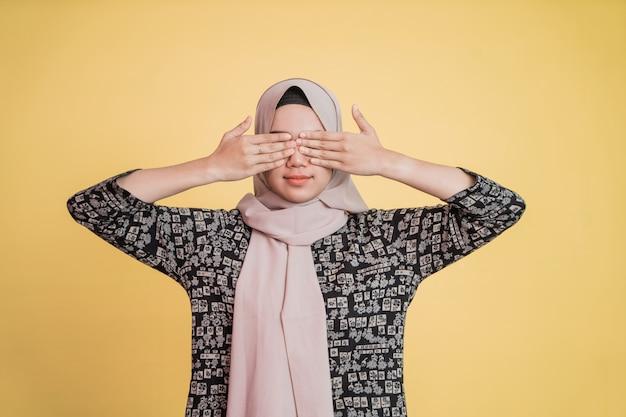 Menina hijab fecha os olhos com as duas mãos